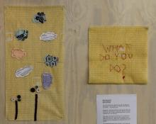 On a wall, two items are next to eachother. The first is a piece of yellow chux cloth with clouds and images sewn on. The second item is the question, sewn in red cloth on yellow chux: What do you do?