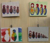 Four frames hang on a wall. They each have slightly different images of babushka dolls.