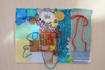 """A colourful collage made of paper, wool, pastels, magazine cutouts. In the top centre of the page is a magazine cutout saying """"Life""""."""