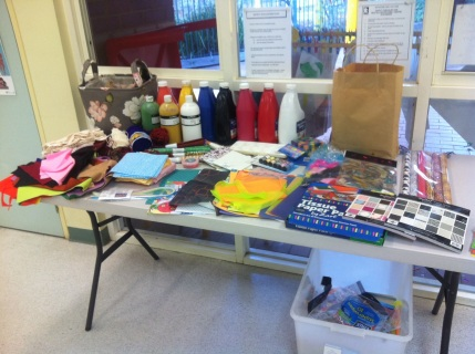 A table covered with an array of items to use: paints, paper, tissue paper, pencils, pens, textas, wool, fabrics.