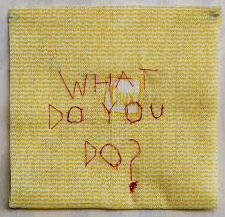 "Yellow chux cloth with ""What do you do?"" hand sewn in red thread"